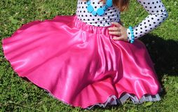 Junges Mädchen, das auf dem Gras, rosa Rock heraus verbreitet in einem Kreis sitzt Lizenzfreies Stockbild