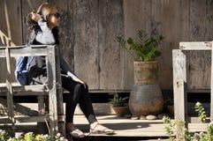Junges Mädchen, das auf dem hölzernen Portal sitzt Stockfotos