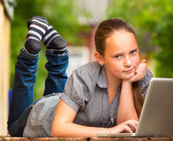 Junges Mädchen, das auf dem Portal des ländlichen Hauses mit einem Laptop liegt. Lizenzfreie Stockfotos