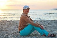 Junges M?dchen, das auf dem Sand durch das Meer bei Sonnenaufgang sitzt stockfoto