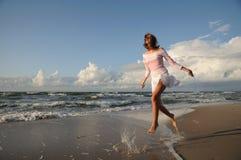 Junges Mädchen, das auf dem Strand überspringt Lizenzfreie Stockfotos