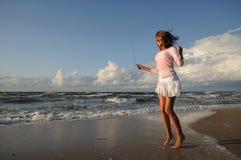 Junges Mädchen, das auf dem Strand überspringt Lizenzfreies Stockfoto