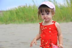 Junges Mädchen, das auf dem Strand isst Lizenzfreies Stockfoto