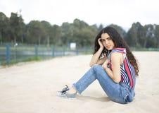 Junges Mädchen, das auf dem Strand sitzt lizenzfreies stockfoto