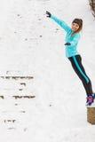 Junges Mädchen, das auf den Schnee springt Stockbild