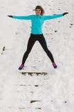 Junges Mädchen, das auf den Schnee springt Lizenzfreies Stockfoto