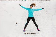 Junges Mädchen, das auf den Schnee springt Lizenzfreies Stockbild