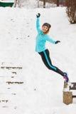 Junges Mädchen, das auf den Schnee springt Lizenzfreie Stockfotografie