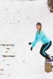 Junges Mädchen, das auf den Schnee springt Stockbilder
