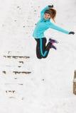 Junges Mädchen, das auf den Schnee springt Lizenzfreie Stockbilder