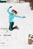 Junges Mädchen, das auf den Schnee springt Lizenzfreie Stockfotos