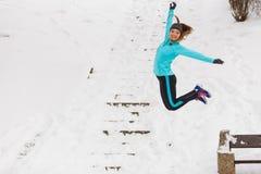 Junges Mädchen, das auf den Schnee springt Stockfotografie