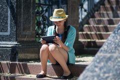 Junges Mädchen, das auf den Schritten sitzt Stockfotografie