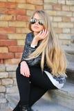 Junges Mädchen, das auf den Treppen in den Sonnenbrillen sitzt Stockfoto