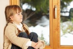 Junges Mädchen, das auf der Fenster-Leiste draußen schaut sitzt Lizenzfreie Stockfotos