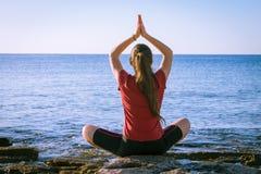 Junges Mädchen, das auf der Küste in der Yogahaltung meditiert Lizenzfreie Stockbilder
