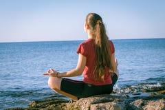 Junges Mädchen, das auf der Küste in der Yogahaltung meditiert Stockfotografie
