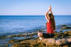 Junges Mädchen, das auf der Küste in der Yogahaltung meditiert Stockfotos