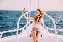 Junges Mädchen, das auf der Yacht sitzt und selfie mit Meer auf dem Hintergrund nimmt Lizenzfreie Stockfotos