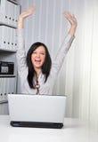 Junges Mädchen, das auf einem Computer zujubelt Stockfoto