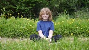 Junges Mädchen, das auf einem Gebiet sitzt Stockfoto