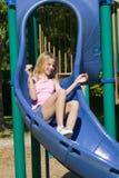Junges Mädchen, das auf einem Plättchen am Park spielt Lizenzfreie Stockfotografie