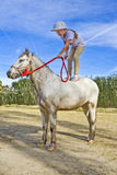 Junges Mädchen, das auf einem Pony steht stockfotos