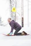 Junges Mädchen, das auf einem Schneeschlitten spielt Stockbild