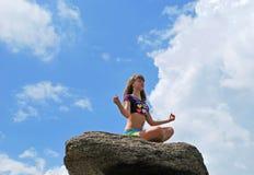 Junges Mädchen, das auf einem Stein sitzt Stockfotografie