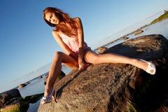 Junges Mädchen, das auf einem Stein sitzt lizenzfreies stockbild