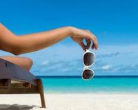Junges Mädchen, das auf einem Strandruhesessel mit Gläsern auf Strand liegt Lizenzfreies Stockfoto