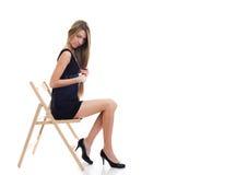 Junges Mädchen, das auf einem Stuhl sitzt Stockfoto