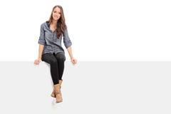 Junges Mädchen, das auf einer leeren Anschlagtafel sitzt Stockfoto