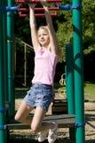 Junges Mädchen, das auf Fallhammerstäben am Park spielt Lizenzfreie Stockfotos