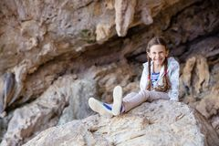 Junges Mädchen, das auf Felsen in kletternden Sektor und im Lächeln sitzt lizenzfreie stockfotos