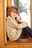 Junges Mädchen, das auf Fenster-Leiste sitzt Stockfoto