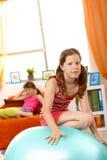 Junges Mädchen, das auf Gymnastikkugel steigt Stockbilder