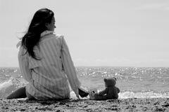 junges Mädchen, das auf leerer Küste sitzt Stockbilder