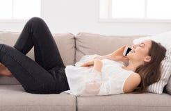 Junges Mädchen, das auf Mobile auf Sofa spricht Lizenzfreies Stockfoto