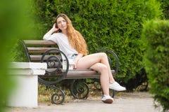 Junges Mädchen, das auf Parkbank stillsteht Stockfoto