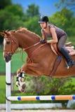 Junges Mädchen, das auf Pferd springt Lizenzfreie Stockbilder