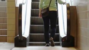 Junges Mädchen, das auf Rolltreppe tritt und oben in Richtung zum Licht umzieht stock footage