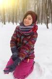 Junges Mädchen, das auf Schnee sitzt Stockbilder