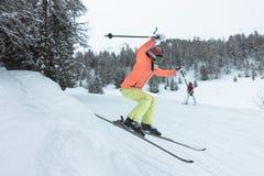 Junges Mädchen, das auf Skis springt lizenzfreie stockfotografie