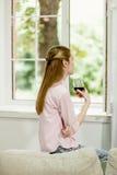 Junges Mädchen, das auf Sofa, nah an dem offenen Fenster, Glas Rotwein halten sitzt stockfotos