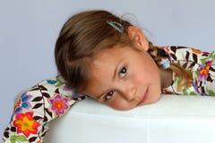 Junges Mädchen, das auf Sofa stillsteht Lizenzfreies Stockbild