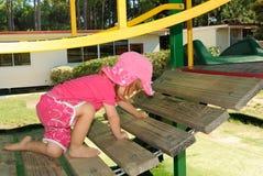 Junges Mädchen, das auf Spielplatz steigt Stockfoto