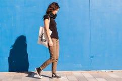 Junges Mädchen, das auf Straße mit blauer Wand im Hintergrund geht Stockfoto