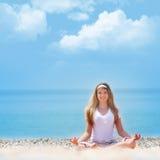 Junges Mädchen, das auf Strand meditiert Stockbild