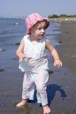 Junges Mädchen, das auf Strand spielt Lizenzfreie Stockbilder